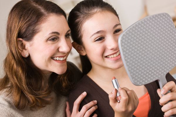 Mother teaching tween daughter to apply lipstick