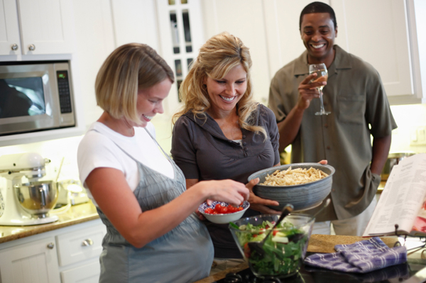 Pregnant Woman in Kitchen with Friends