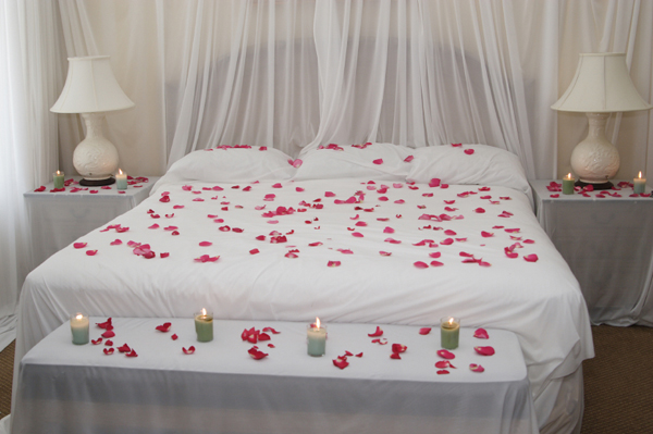 Romantic Bedroom with Candles and Rose Petals