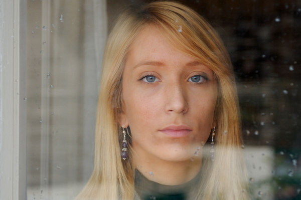 Sad woman looking through winter window