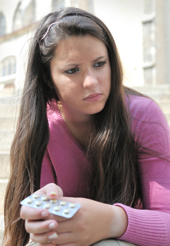 Teen girl taking diet pills
