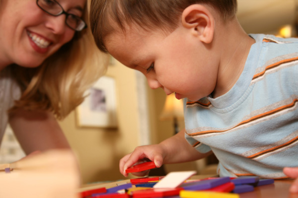 Toddler boy playing with blocks. How much do you spend on childcare?