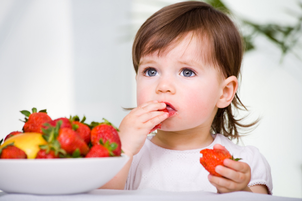 Toddler girl eating strawberry