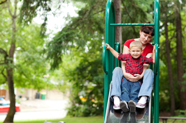 Toddler on Mother's Lap going down slide