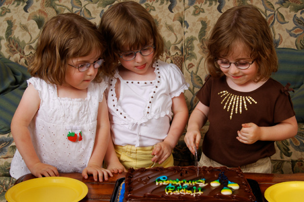 Triplets cutting birthday cake