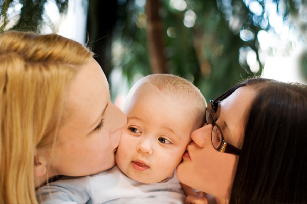 Two women kissing baby