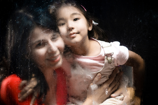Woman and daughter looking through rainy window