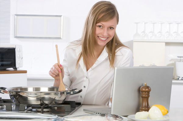 Woman cooking near laptop
