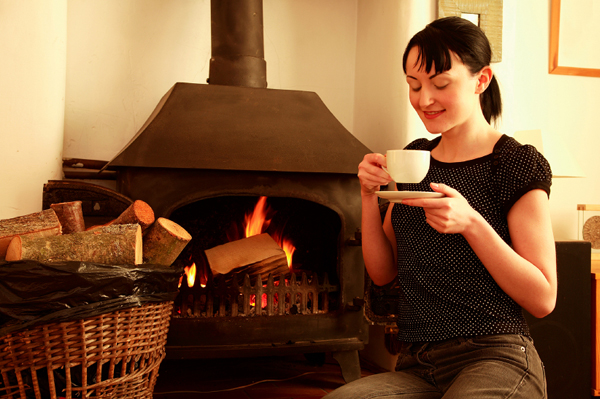 Woman drinking herbal tea by fireplace