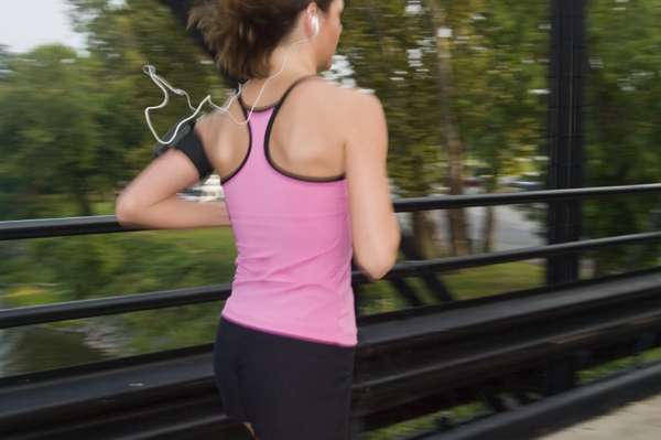 Woman with earbuds running over bridge