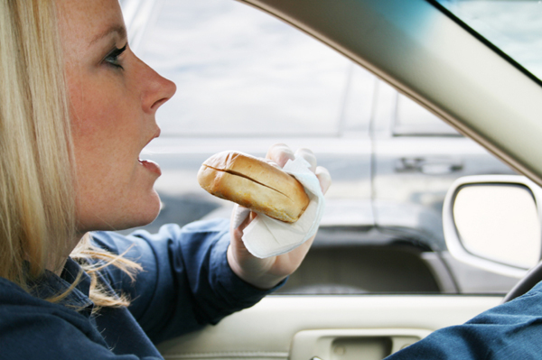 Woman eating bagel in car.
