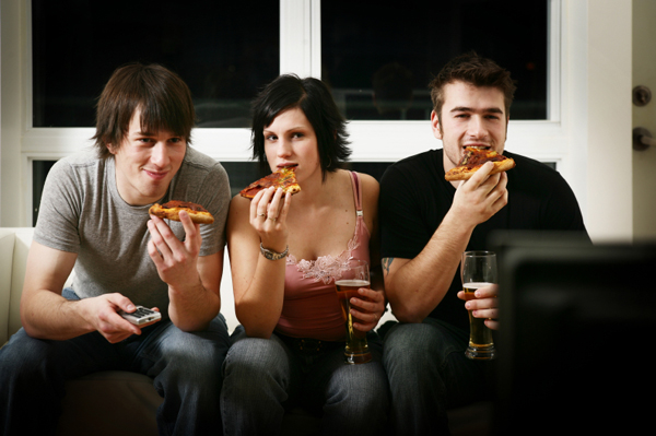 Woman eating pizza in front of TV