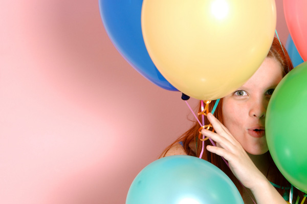 Woman hiding behind balloons