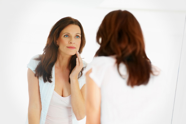 Woman in forties looking in mirror