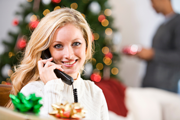 Woman on phone in front of a Christmas tree