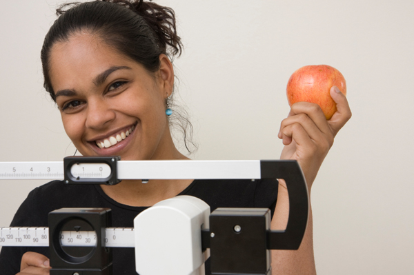 Woman on Scale with Apple