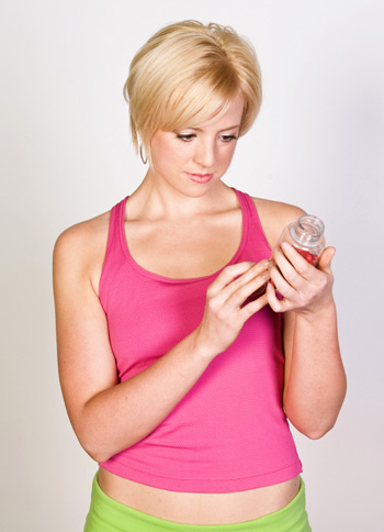 Woman Reading Label of Vitamin Bottle