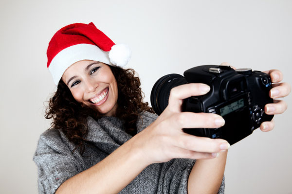 Woman wearing santa hat with camera