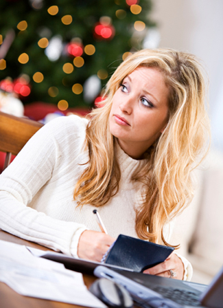 Woman Writing Check in front of Christmas Tree