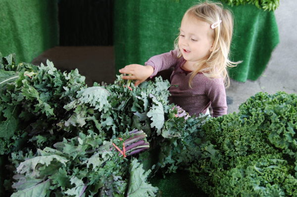 Young girl with leafy green organic vegetables