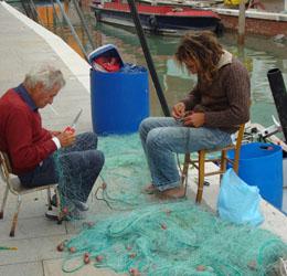 fishermen repairing nets in Burano, Italy