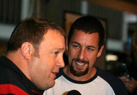 Adam Sandler smiling and looking at Kevin James