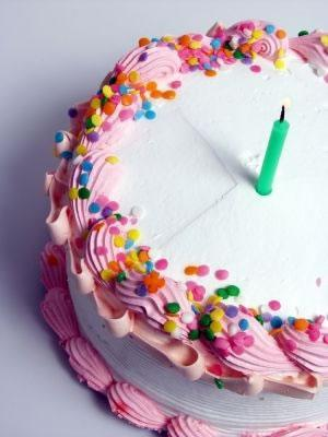 White frosted cake with pink trim and rainbow sprinkles