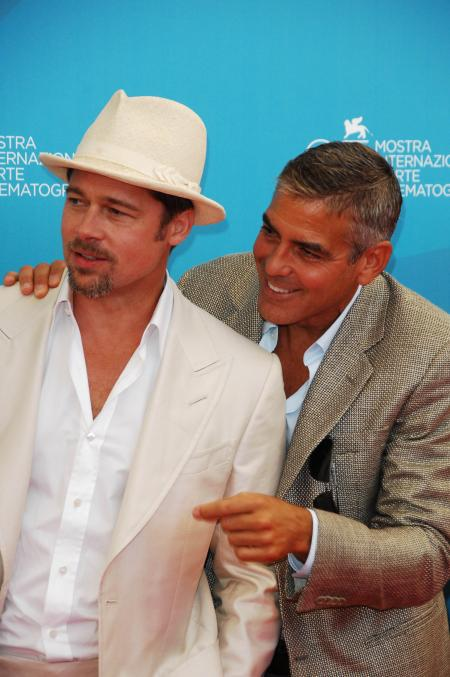 George Clooney points next to Brad Pitt at the Venice Film Festival