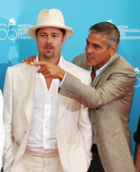 George Clooney has his hand on Brad Pitt's shoulder at a film festival