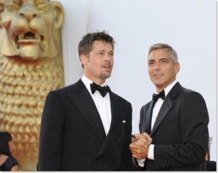 Brad Pitt and George Clooney in front of a golden lion while in Venice