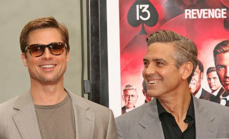 Brad Pitt smiles standing next to George Clooney at Gauman's Chinese Theatre
