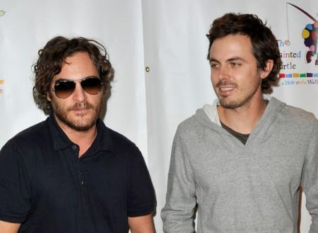 Joaquin Phoenix in sunglasses next to Casey Affleck in San Francisco