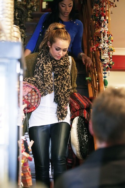 Miley Cyrus pairs her leather pants with a subtle leopard print scarf.