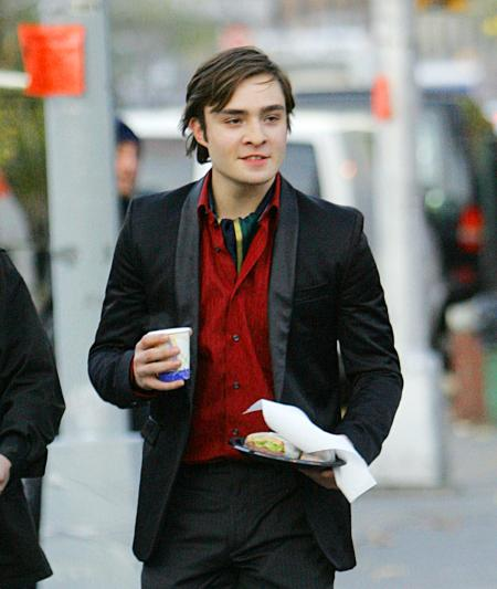 Ed Westwick is carrying food and a drink during a break