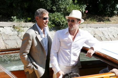 George Clooney leaning with Brad Pitt in Venice