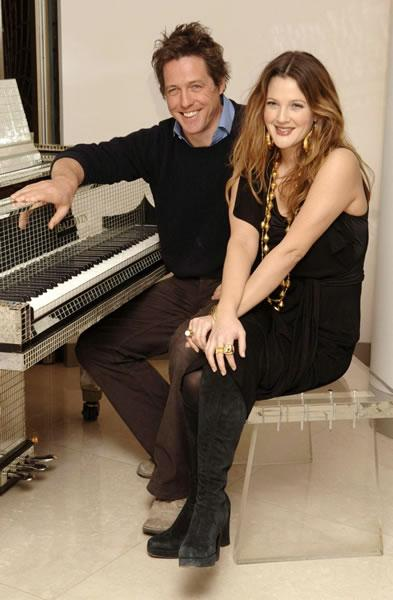 Hugh Grant and Drew Barrymore pose in front of a piano during a photocall for their film 'Music and Lyrics.'