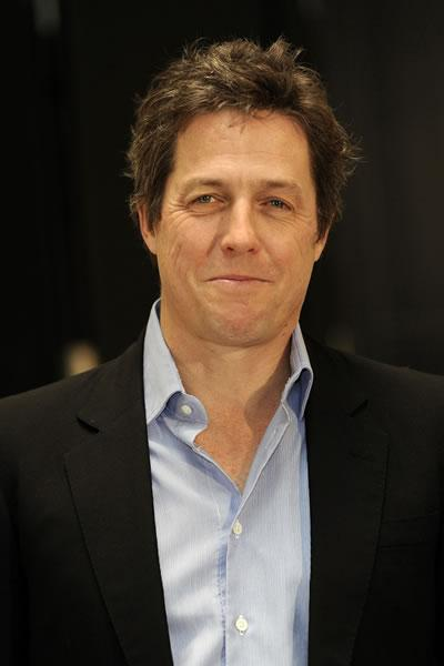 Hugh Grant smirks at a photocall for his film 'Did You Hear About the Morgans?' in Germany.