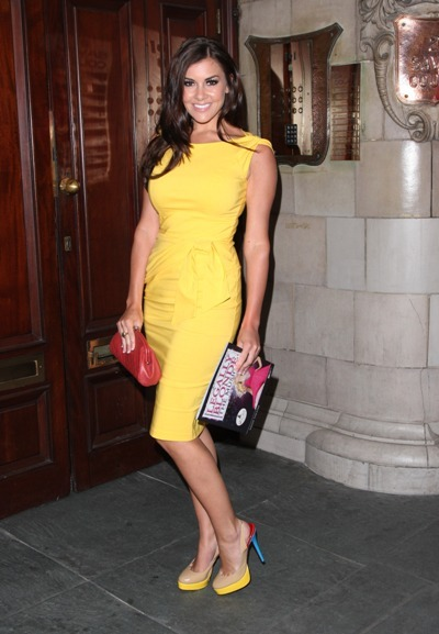 Imogen Thomas smiles for the camera in yellow dress