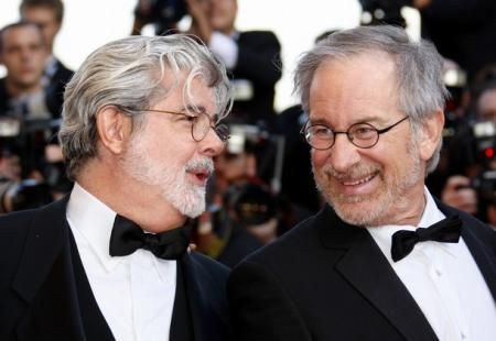 Spielberg and Lucas share a word during a movie premiere