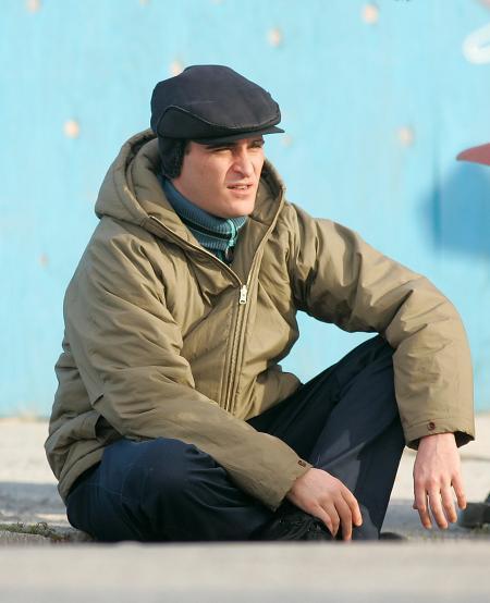 Joaquin Phoenix sits on the ground