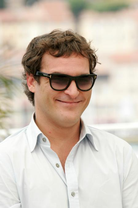 Joaquin Phoenix is wearing sunglasses and smiling