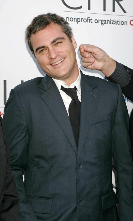 Joaquin Phoenix with a dark suit and black tie at a nonprofit organization event