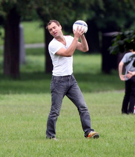 Jude Law in the grass holding a soccer ball while in London