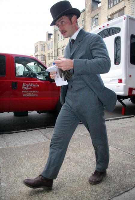 Jude Law walks down the street in Sherlock Holmes