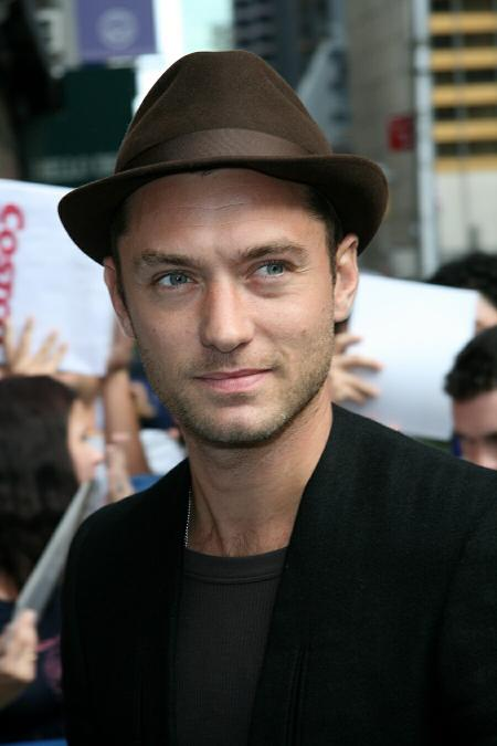 Jude Law wears a dark shirt and a brown hat in New York City