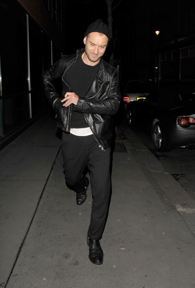 Jude Law struts his stuff in a black leather jacket and beanie