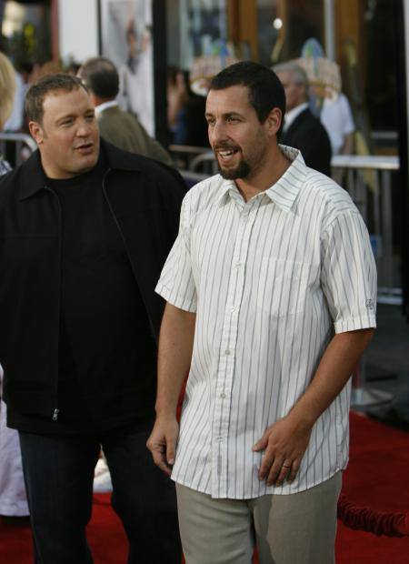 Kevin James says something to Adam Sandler on the red carpet