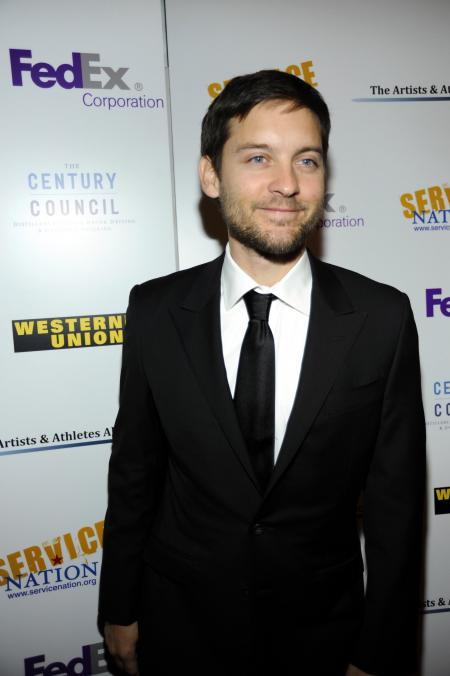 Tobey Maguire smiles for the camera in a suit at a Service Nation event