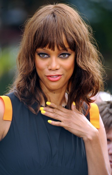 Tyra Banks with yellow fingernails
